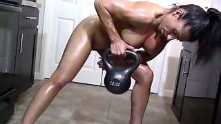 Oiling muscles in her kitchen